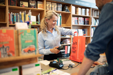 Female bookstore cashier helping customer