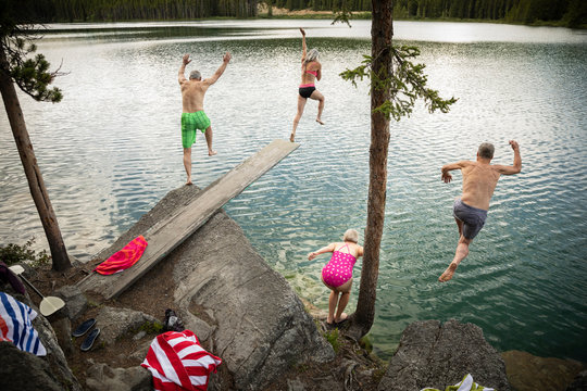Mature couples jumping off diving board and rocks into lake