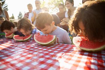 Kids enjoying watermelon eating contest at summer neighborhood block party in park