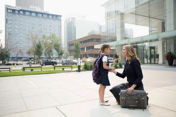 Businesswoman mother and schoolgirl daughter talking on urban sidewalk