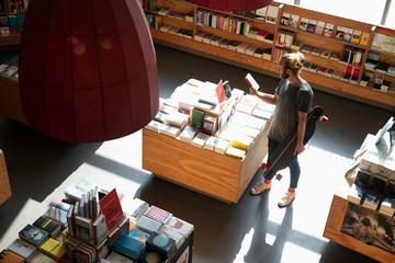 Man with skateboard shopping in bookstore