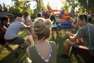 Woman clapping, watching neighbors playing tug-of-war at summer neighborhood block party