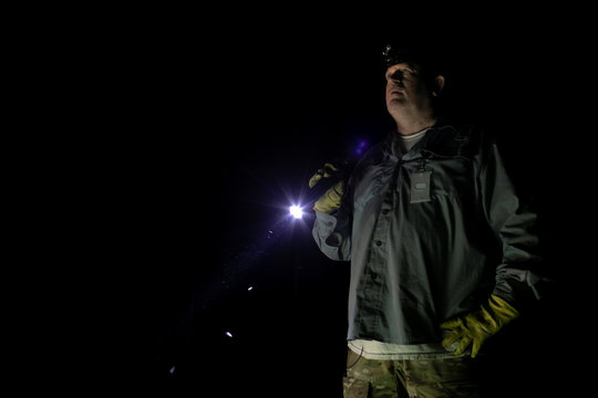 Thomas Aycock uses a flashlight as he explores the Everglades' swamps looking for Burmese pythons, in Ochopee