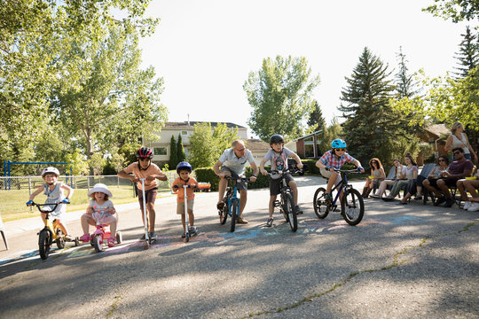 Kids ready for bike race at starting line at summer neighborhood block party