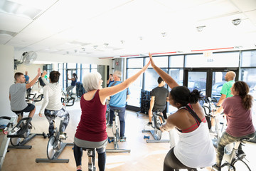 Women high-fiving in spin class in gym