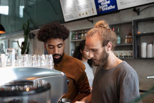 Male baristas using espresso machine in cafe