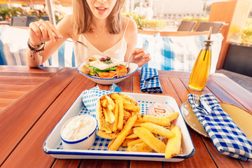 Cheerful tourist girl tries Greek cuisine at a local restaurant. On the table traditional salad...