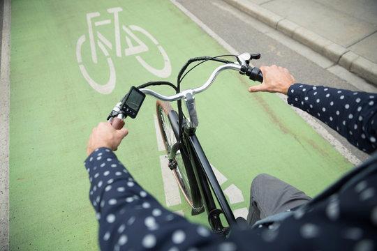 Businessman commuter riding bicycle in urban bike lane