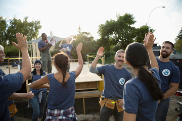 Enthusiastic volunteers high-fiving and celebrating, helping build house