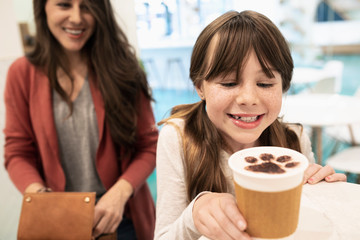 Mother and daughter ordering coffee with chocolate paw foam in cat cafe