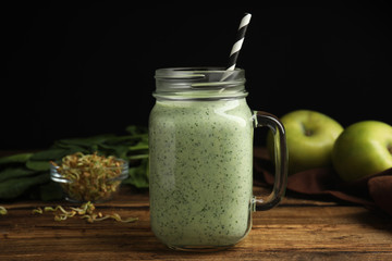 Tasty green buckwheat smoothie on wooden table