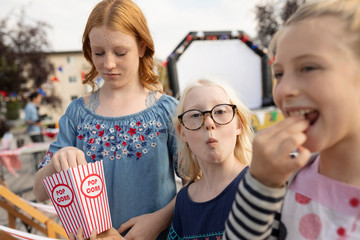 Portrait sisters enjoying popcorn at movie in the park