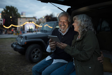 Senior couple with digital tablet at back of SUV at night