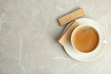 Breakfast with delicious wafers and coffee on grey marble table, flat lay. Space for text
