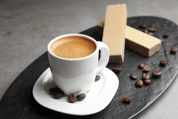 Delicious coffee and wafers for breakfast on grey table