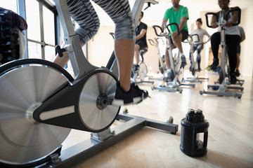 Water bottle on floor next to spin class instructor on exercise bike