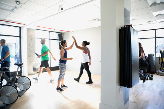 Women high-fiving after spin class in gym