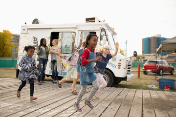 Playful, excited girls running outside ice cream truck
