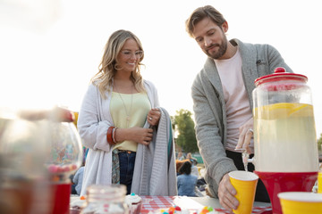 Couple pouring lemonade at movie in the park
