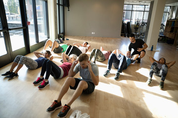 Group exercise class doing sit-ups in gym studio