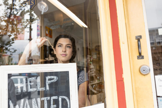 Female small business owner placing Help Wanted sign in shop window