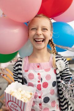 Portrait enthusiastic, laughing girl with popcorn and balloons