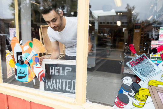 Male business owner placing Help Wanted sign in art supply shop window