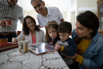 Latinx multi-generation family looking at photo album