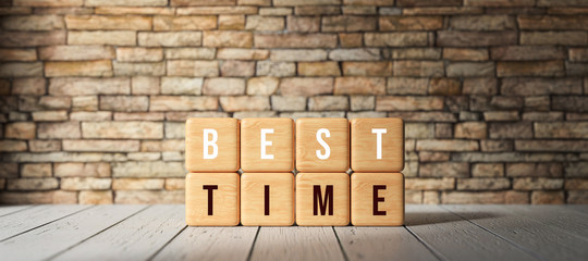 cubes with the words BEST TIME in front of a brick wall on wooden surface