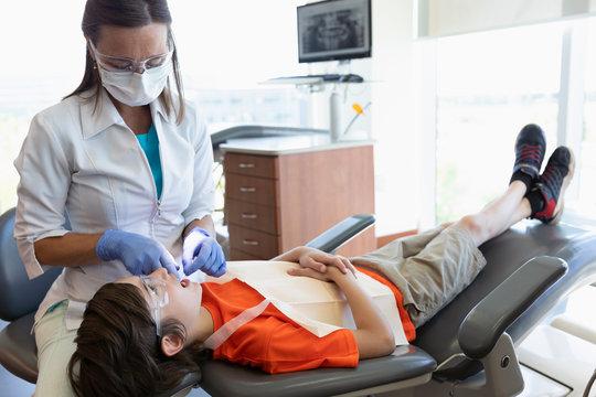 Dental hygienist flossing teeth of boy in dentist office