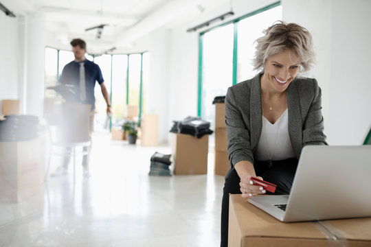 Businesswoman with credit card paying bills at laptop in new office with cardboard boxes
