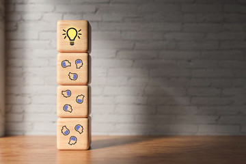 cubes with the person-symbols and lightbulb symbols in front of a brick wall
