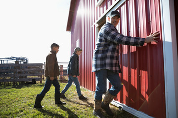 Farmer and sons opening barn door on sunny farm