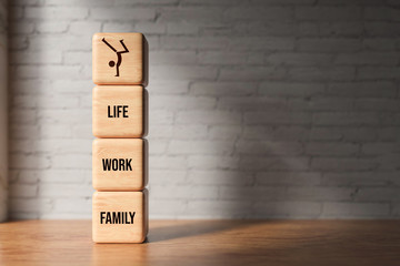 wooden blocks with the words FAMILY, WORK and LIFE on wooden background