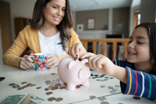 Mother watching son place coins in piggy bank