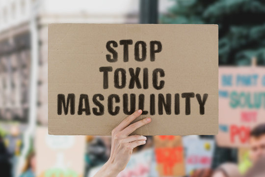 "The phrase "" Stop toxic masculinity "" on a banner in men's hand. Human holds a cardboard with an inscription. Male abuse. Homophobia. Problem. Real man. Respect. Social issues. Equality. Justice"