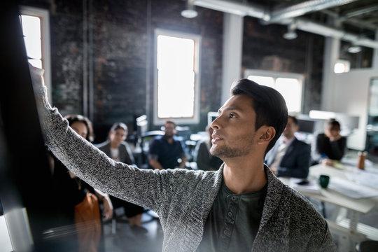 Creative businessman leading meeting in loft office