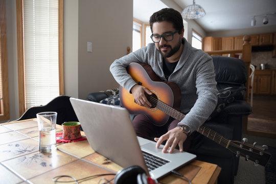 Latinx man playing guitar at laptop