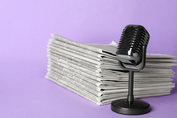 Newspapers and vintage microphone on light violet background. Journalist's work