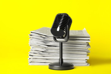 Newspapers and vintage microphone on yellow background. Journalist's work