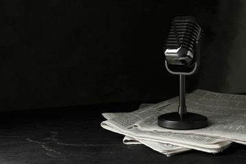 Newspapers and vintage microphone on dark stone table, space for text. Journalist's work