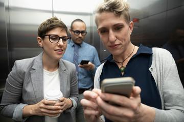Business people using smart phones in elevator