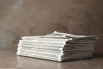 Stack of newspapers on marble table. Journalist's work