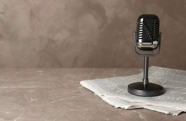 Newspapers and vintage microphone on marble table, space for text. Journalist's work