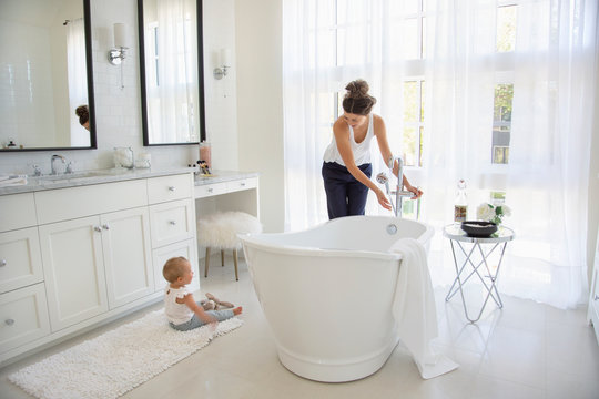 Mother and baby daughter preparing bath