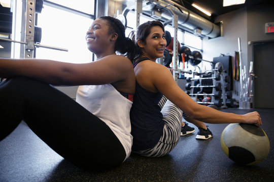 Smiling women with medicine ball sitting back to back, resting in gym