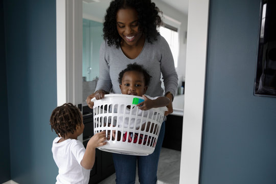 Mother carrying baby son in laundry basket