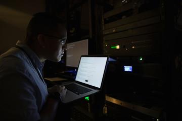 IT technician using laptop in dark server room