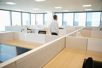 Businessman standing among cubicles in new office