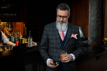 Stylish hipster businessman in suit drinking cocktail and checking smart phone in bar